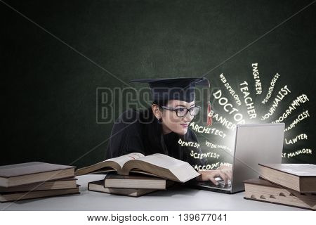Female student wearing a graduation cap while typing her dream job on the laptop with book on desk