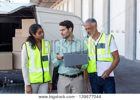 Manager is talking and showing something on laptop to the workers in front of a warehouse