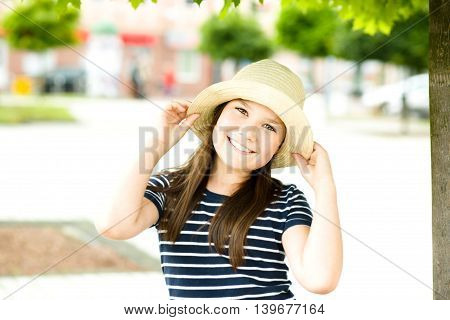 Portrait of a beautiful girl in bright hat