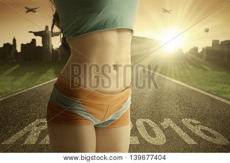 Close up of tummy of female athlete with text Rio 2016 on the road