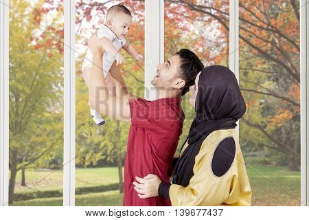Two young muslim parents smiling happy while playing with their baby at home with autumn background on the window