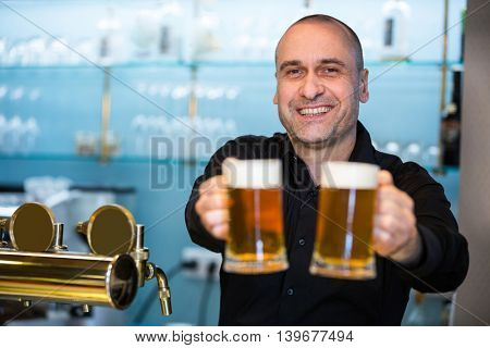Portrait of happy bar tender offering beer at bar