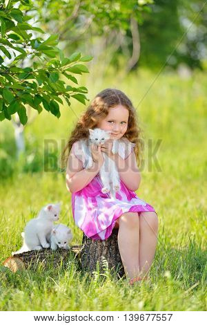 Adorable little cyrly girl playing with small kittens at warm and sunny summer day. Happy smiling kid holding pets.