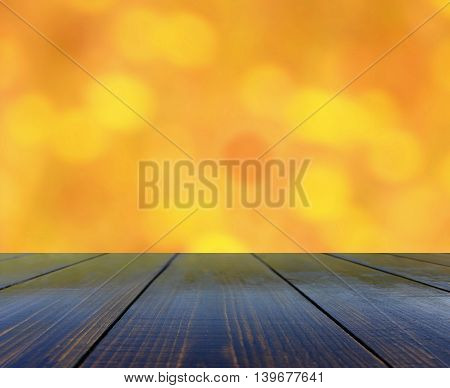 table from wooden boards with blurred brown background with yellow spots