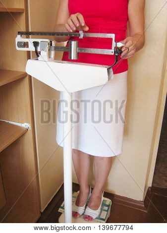 woman is weighed on the old mechanical scales