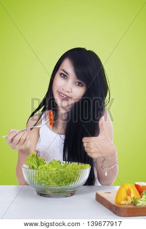 Beautiful young woman with long hair eating a bowl of salad while showing thumb up