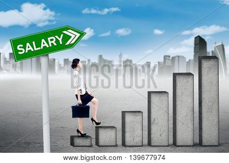 Female worker walking on the graph with salary text on the signpost