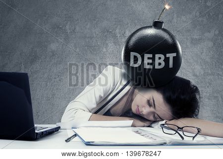 Stressful businesswoman sleeping on desk with a text of debt on the bomb at her head