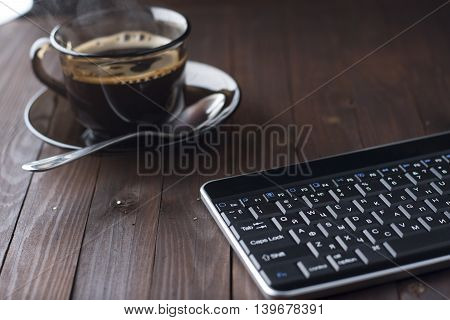 The Keyboard Is On A Wooden Table, Standing Next To A Cup Of Coffee.