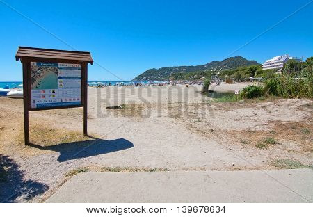 CANYAMEL MALLORCA BALEARIC ISLANDS SPAIN - JULY 19 2016: Entrance sign to Canyamel beach with sun lounge chairs on a sunny day on July 19 2016 in Palma de Mallorca Balearic islands Spain.
