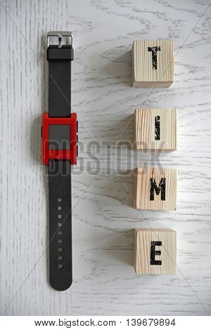 Word TIME with wristwatch on wooden background