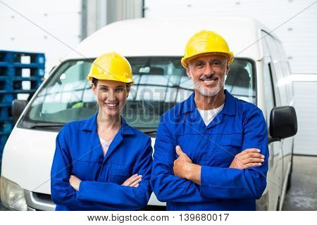Smiling workers crossing arms in warehouse