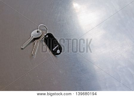 Door keys on stainless steel table and skylight in reflection concept