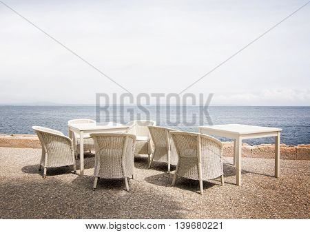 White rattan furniture in white gravel with horizon view over Mediterranean sea Mallorca in June.