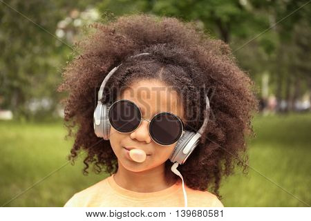 Afro-American little girl with sunglasses and headphones chewing bubblegum in park