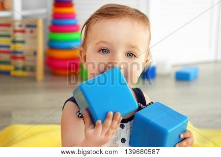 Baby with bright toy blocks in child room