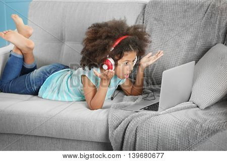 Cute African girl with laptop on couch