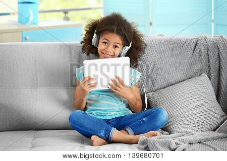 Cute African girl with tablet on couch