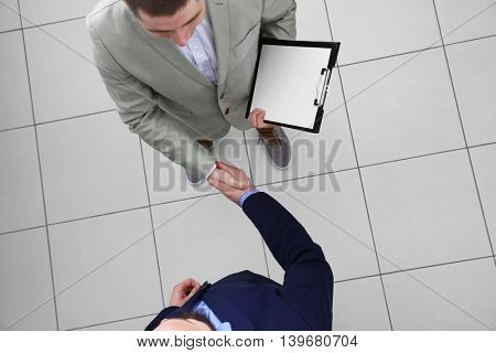 Two businessmen shaking hands on grey background