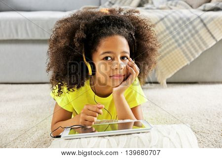 Afro-American little girl with headphones and tablet lying on floor