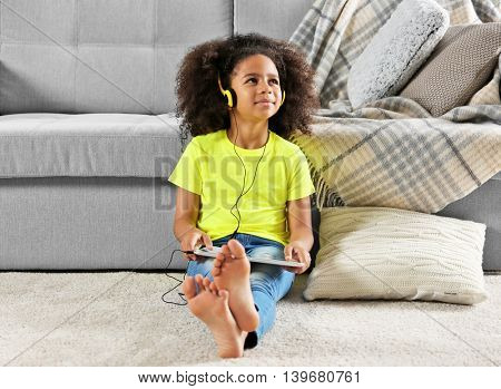 Afro-American little girl with headphones and tablet sitting on  floor