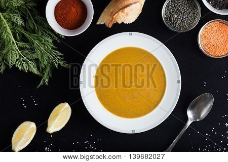 Cream soup of assorted lentil. Yellow and green lens spices as raw for meal and lemon on black backgraund. Healthy appetizing delicious vegetarian food. Top view copy space.