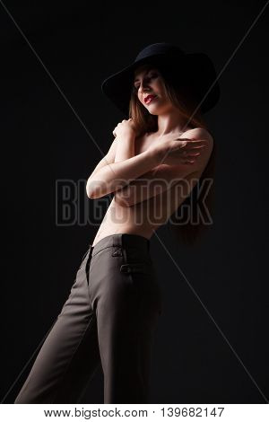 Portrait of attractive young girl in black hat covering naked breast while looking away.Studio shot
