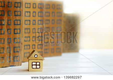 retro small house surrounded by a multi-storey skyscrapers at sunset