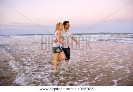 Couple Walking On The Beach At Dusk