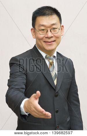 An asian business man extending his hand for a hand shake