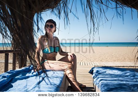 Beautiful young girl in bungalow with black sunglasses in blue swimsuit. View on the sea.