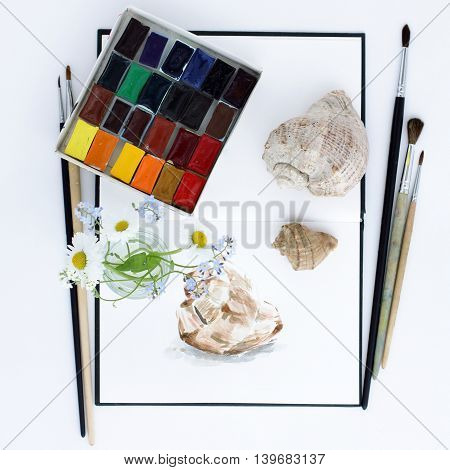 Art objects notebook paint brush flowers and seashells flat lay top view