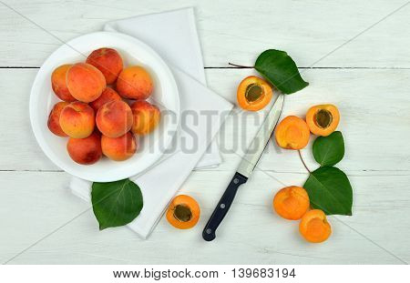 Apricots. Dish of harvested apricots on a wooden surface top view rustic style. Appetizing background of summer fruits.