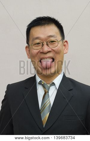 An asian business man showing his tongue