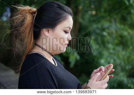 young asian woman texting and looking at her smartphone