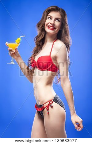 Side view of young beautiful brunette in bright red and blue bikini with exotic cocktail smiling back.Isolate.