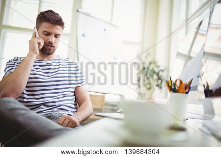 Young businessman using mobile phone while sitting in office