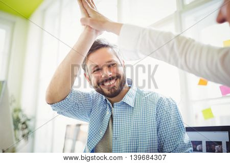 Smiling coworkers giving high-five at desk in creative office