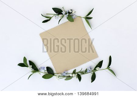 flat lay background with spring flowers as a frame and blank sheet for congratulations top view/ congratulatory card invitation