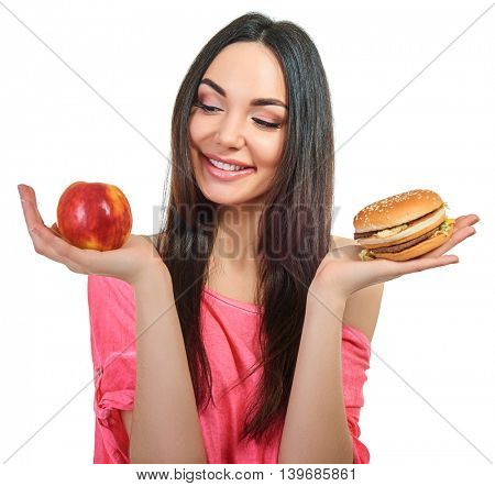 Young woman with fast food and apple. Girl makes choice between healthy and unhealthy eating.