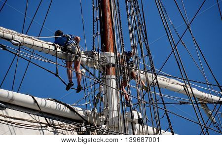 Mystic Connecticut- July 11 2015: Crew members high atop the yardarms opening the sails of the 1841 Charles W. Morgan whaling ship at Mystic Seaport Museum
