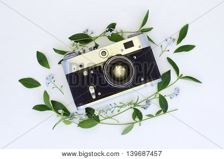 old retro film camera in the flowers and leaves of a top view / cover on the photo album