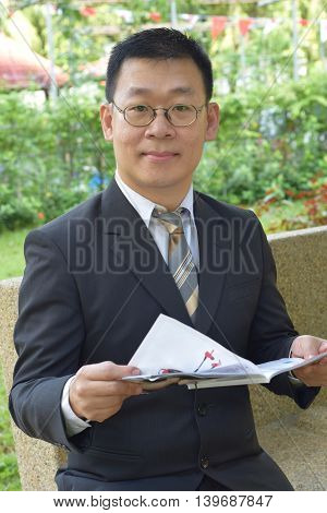 An asian man looking at the camera while holding a magazine