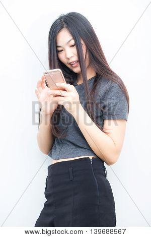 Smiling Asian Charming  Woman Is Using On Smartphone Texting