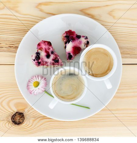 background with coffee and berry cake in the form of hearts top view / flavored holiday dish for couples