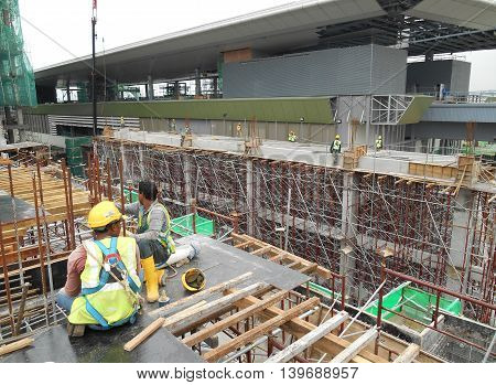 MALACCA, MALAYSIA -MAY 25, 2016: Construction workers fabricating timber form work at the construction site in Malacca, Malaysia. The form work was mainly made from timber and plywood.