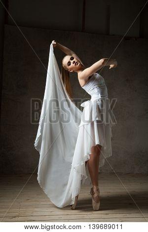 Portrait of attractive young blonde ballet dancer in white costume dancing in studio