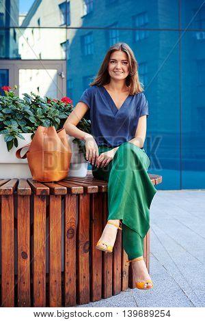 Elegantly dressed young attractive woman is sitting on round bench with flower pot and smiling against modern building background
