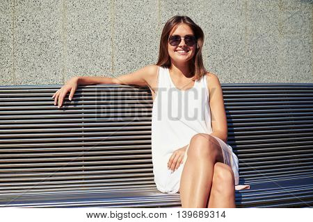 Young beautiful woman in sunglasses is sitting on bench near building wall and smiling at the camera