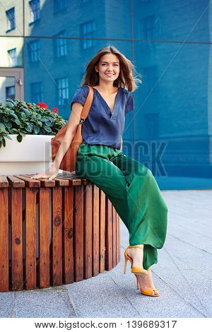 Attractive female in stylish elegant clothes is sitting on round bench with flower pot and posing at the camera in downtown